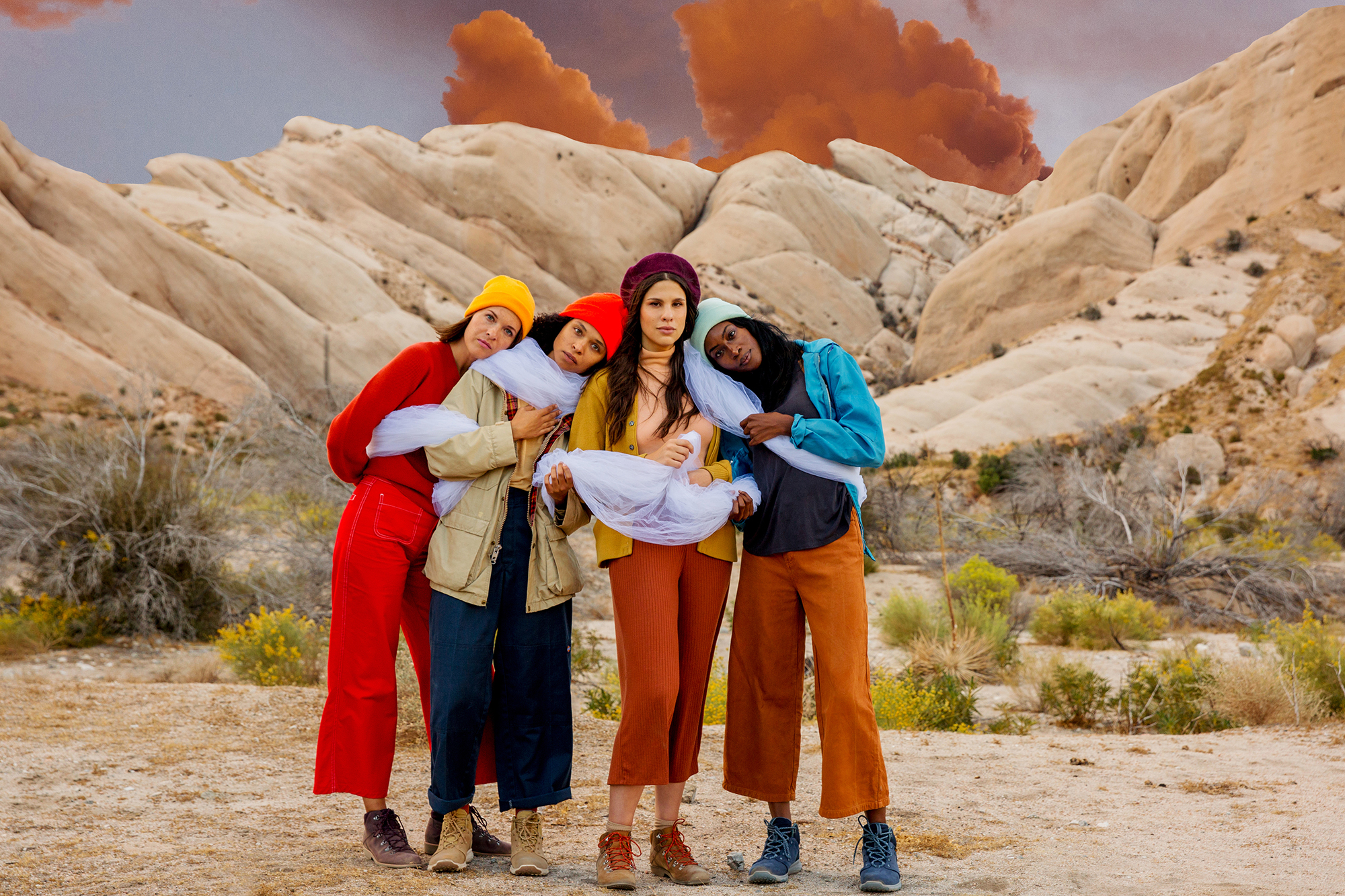 Four women standing together in the desert wearing colorful clothing