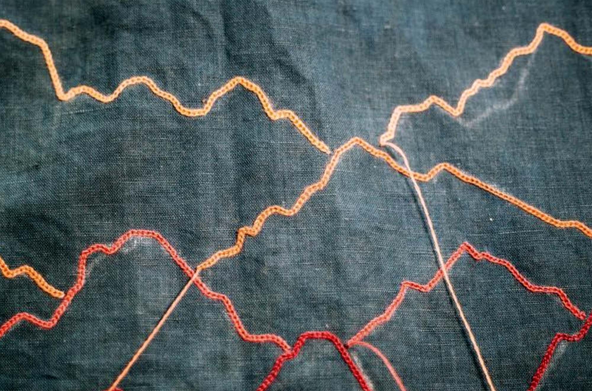 Detail shot of mountains stitched in colored embroidery thread.